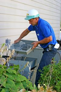 technician working on outside unit of an air conditioner